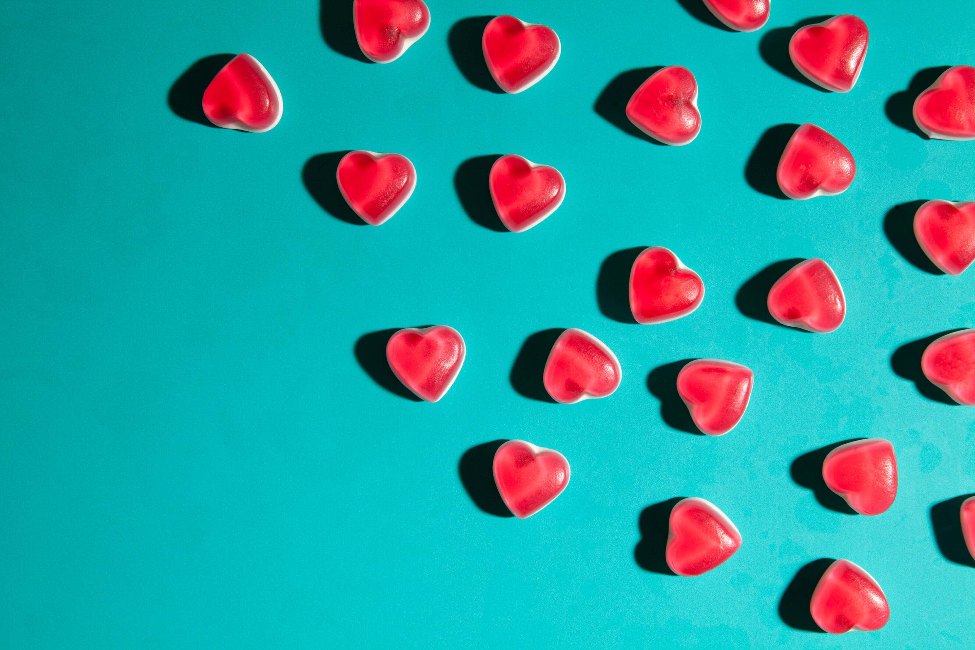 Love heart Haribo sweets photographed from above on a turqoise background with hard shadows for a pop art effect.