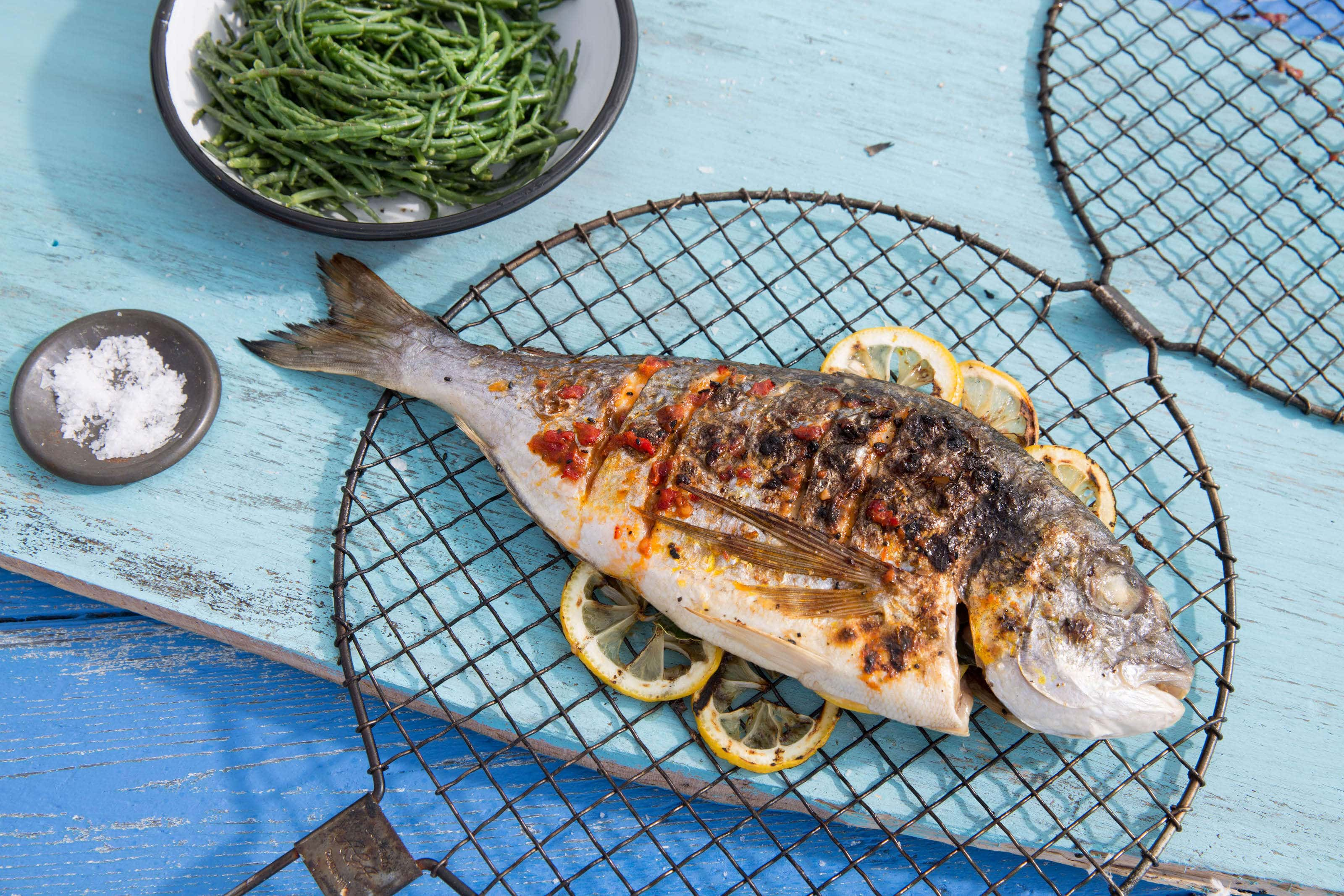 Cooked Sea bream on a turquoise table with salt and samphire.