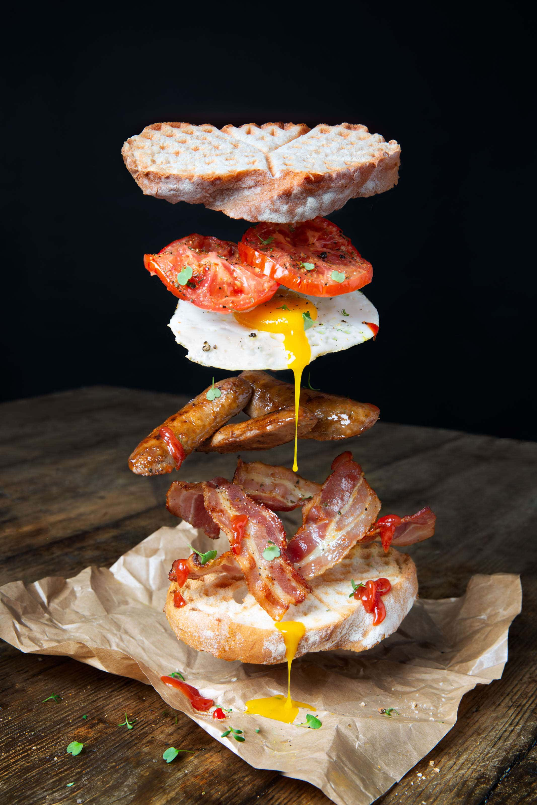 an egg, bacon and sausage sandwich with tomatoes with all ingredients floating above the other. Floating food.